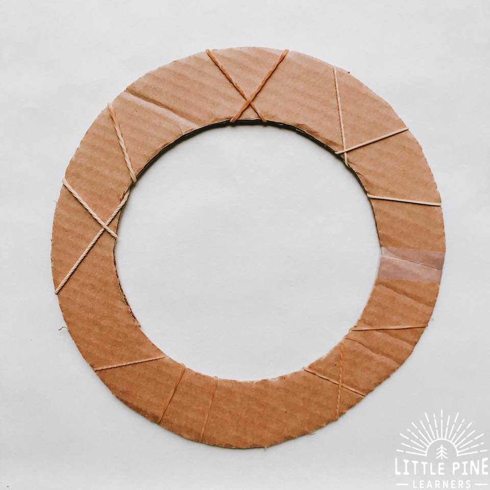 Try making this simple and adorable holiday wreath for kids! This nature craft features real pine branches and cardboard, making it a great eco-friendly Christmas craft or gift. Kids will love making their wreaths while working on fine motor skills.