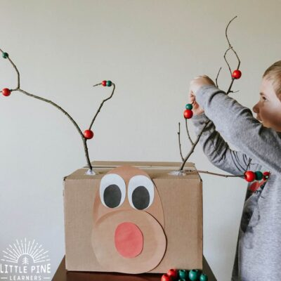 Check out this adorable recycled box reindeer activity for preschoolers! It's the perfect activity to help strengthen fine motor muscles and work on early math skills. Kids will love threading the beads on rudolf's stick antlers while they work on making patterns, counting, sorting, and color recognition! There's a lot of learning going on in this super simple activity.