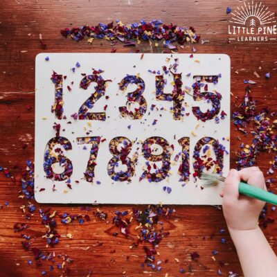 Try using these hands-on alphabet and number tracing boards with your favorite nature sensory bin filler for a fun way to learn how to write numbers and letters! Children will love tracing the numbers and letters and sweeping the flower confetti pieces into the tracing board with a paint brush.