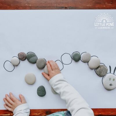 Here is a great stone activity for kids! This is the perfect spring game for kids and makes a great extension activity for The Very Hungry Caterpillar. Kids will enjoy searching for the correct stones while learning new nature vocabulary words, strengthening fine motor skills, and comparing different stone sizes and shapes.