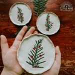 Clay dish with evergreen pieces.